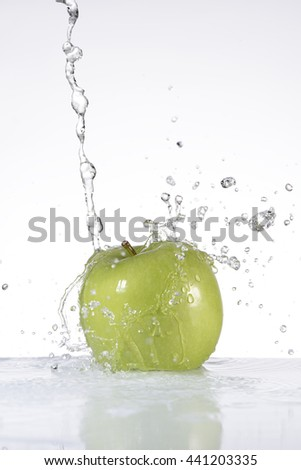 Water falling on an apple on white background