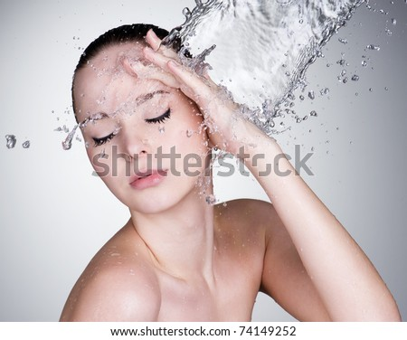 Water falling on the beautiful sensuality woman face with clean skin - horizontal - stock photo
