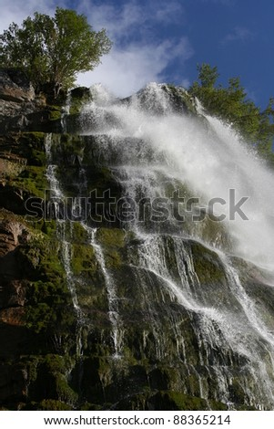 Water falling over rocks covered with green moss and grass, with blue sky in the background (Bridal Veil falls in Utah, USA). - stock photo