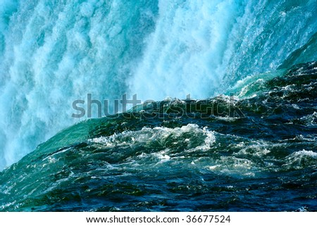 Water falling over the cascade and glimmering in the sunlight - stock photo
