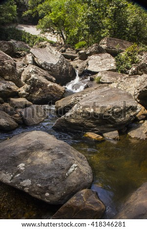 Water falls between rocks in sunny day
