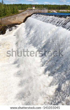 Water falls from dam overflow. Man made water reservoir , - stock photo