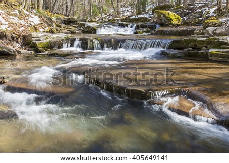 Water falls gently over rocky strata on the West Kill in the Catskills Mountains of New York. - stock photo