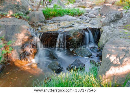 Water falls over a jumble of moss-covered boulders in forest. - stock photo