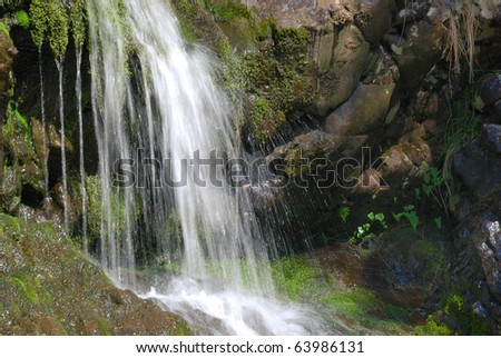 Water falls over moss covered rocks.