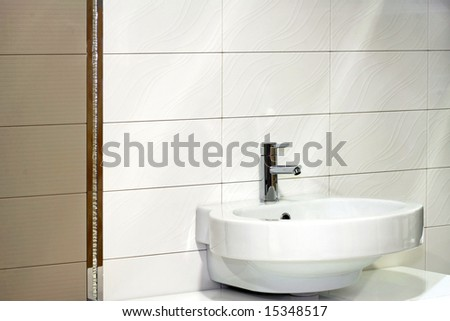 Water faucet in silver and white basin - stock photo