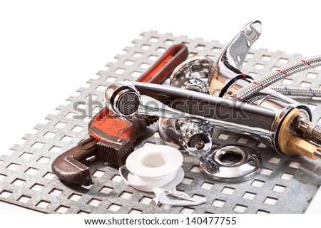 Water faucet, pipe wrench, on a metal grid on a white background