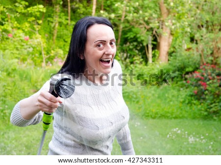water fight, smiling, laughing woman aiming running hosepipe in garden. landscape. - stock photo