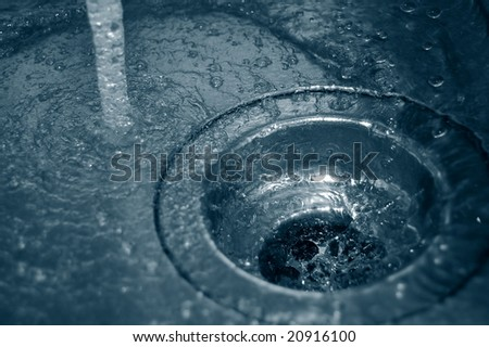water flow into the drain in the kitchen - stock photo