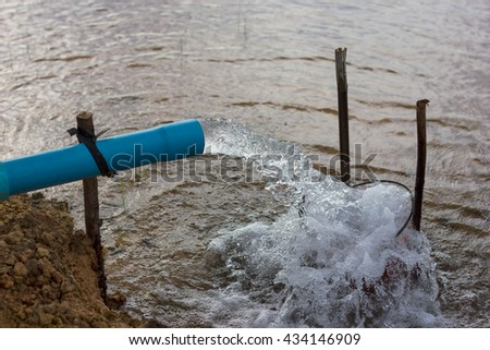 Water flow out of the pipe pumping fast, which is tied to a tree stump sticking out in the rice fields. - stock photo