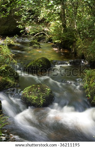 Water flowing around rocks in a mountain stream - stock photo