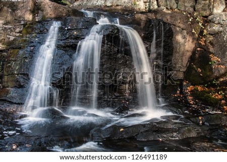 Water flowing at full force at a waterfall - stock photo