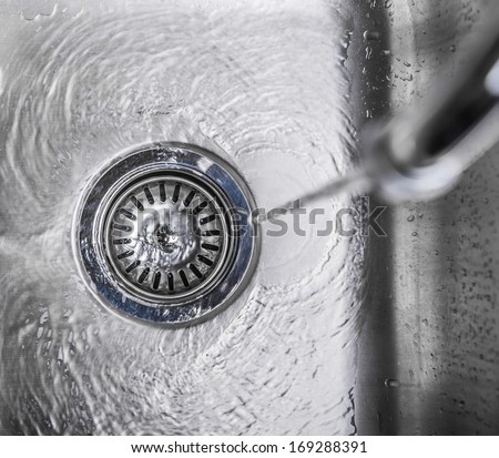 Water flowing down the hole in a kitchen sink