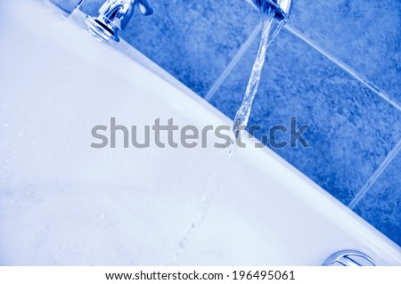 Water flowing from a faucet and into a tub. - stock photo