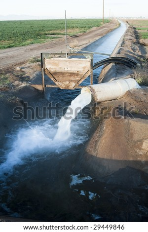 water flowing from a pipe into an irrigation canal - stock photo