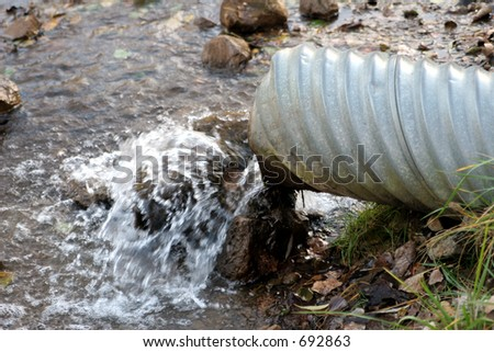 Water flowing from drain pipe - stock photo