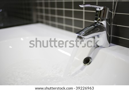 water flowing from the tap in the bathroom - stock photo