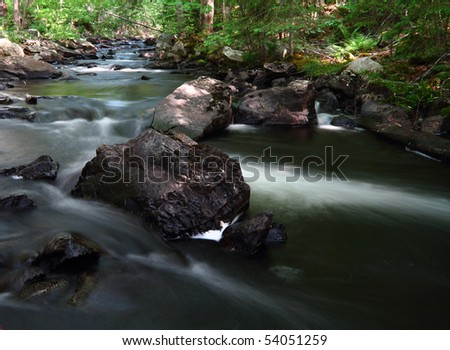 Water flowing in a forest stream in dappled sunlight - stock photo