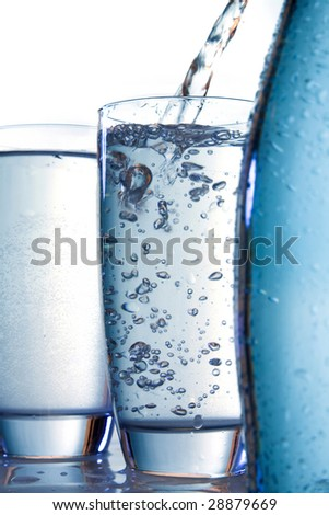 water flowing in a glass and a bottle