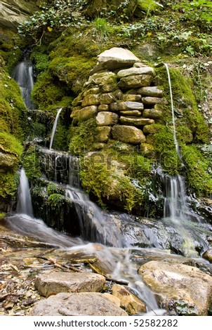 Water flowing on natural stones moss-grown