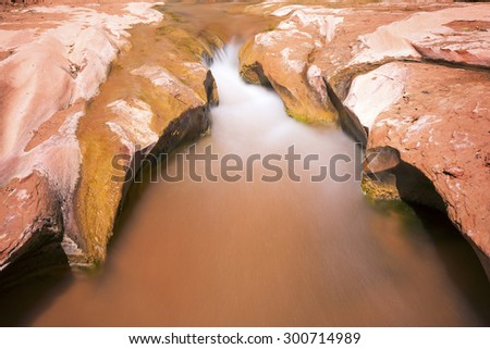 Water flowing on red rock in Coyote Gulch, Utah.