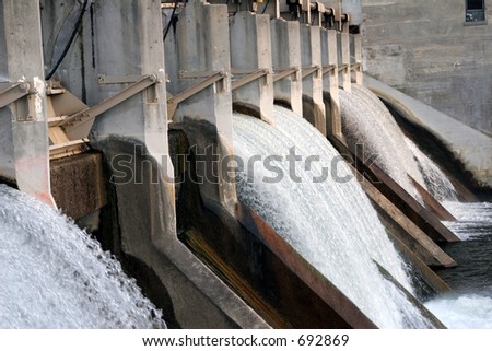 Water flowing over electric dam - stock photo