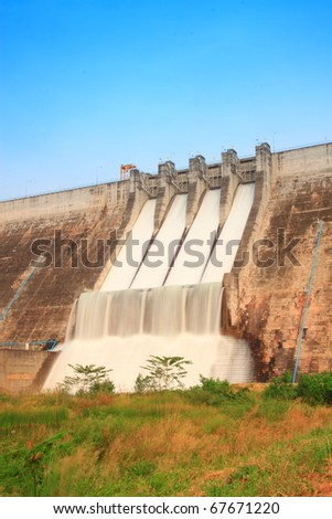 Water flowing over flood gates of a dam - stock photo