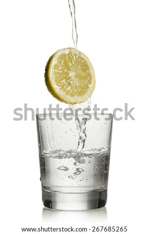 water flowing over lemon and fill a glass on white background - stock photo