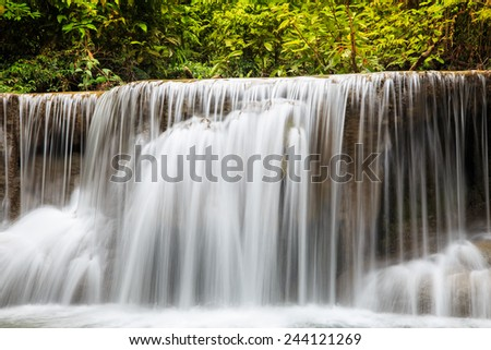Water flowing over rocks in waterfall cascade in a forest - stock photo