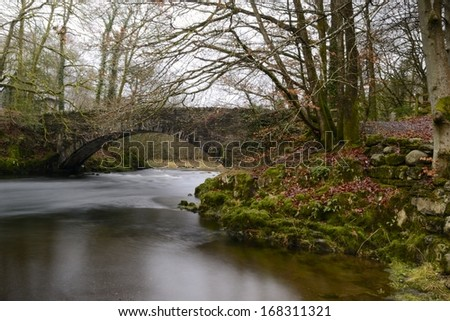 Water flowing under the old stone bridge as the fog lifts near Ambleside, Lake District, England. - stock photo