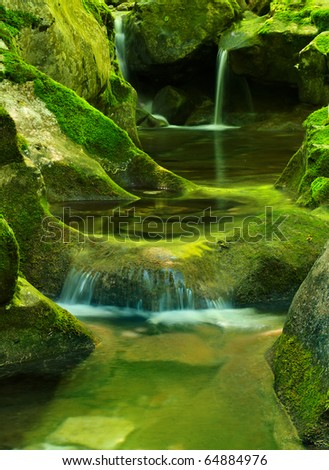 Water flows amongst stone built cascade - stock photo