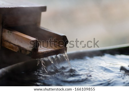 Water flows at a japanese open air hot spring (onsen) - stock photo