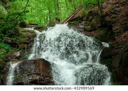 Water flows from a waterfall in the green forest horizontal photo