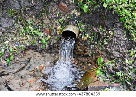 Water flows from the pipe - stock photo