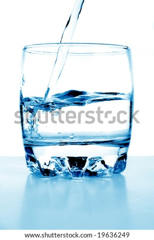 Water flows in a glass. - stock photo
