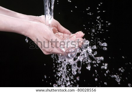 Water flows in female palms (a black background) - stock photo