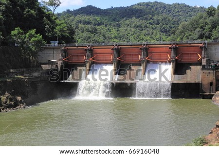 water flows over dam - stock photo