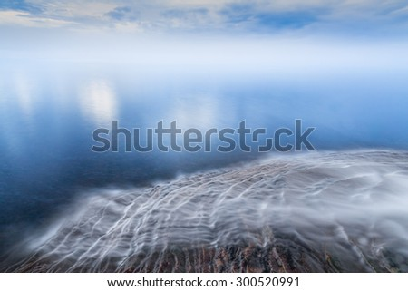 Water flows over the sandstone ledges of Michigan's northern coast and into Lake Superior with a cloud-draped horizon. Elliot Falls is in Pictured Rocks National Lakeshore near Munising, Michigan. - stock photo