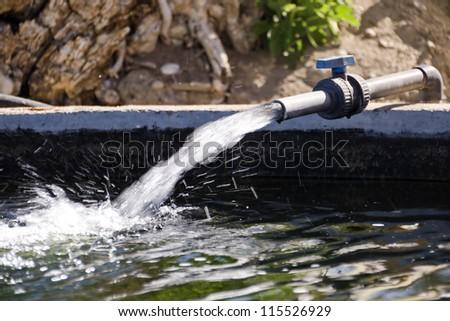 Water from a well filled a pond for irrigation - stock photo