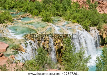Water from Havasu Creek flows over travertine pools and rushes over Little Navajo Falls on the Havasupai Indian Reservation in the Grand Canyon. - stock photo
