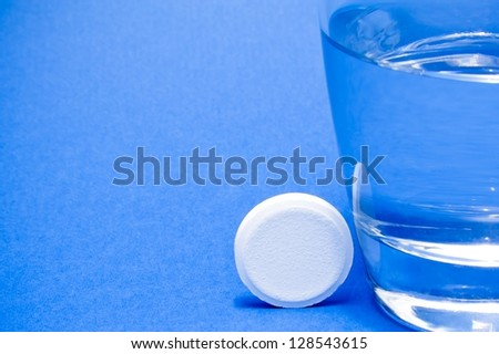 water glass near a tablet on blue background - stock photo