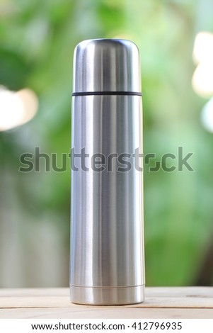 Water glass of aluminum (Aluminum mug) on wooden floor and have green color nature in backdrop.