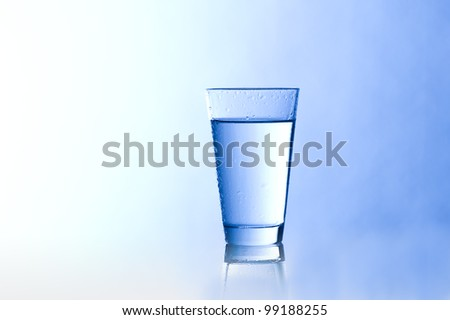 Water glass with a grow background - stock photo