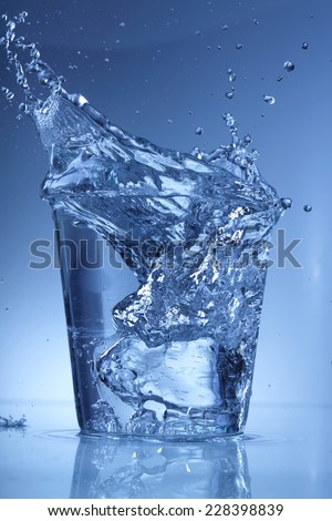 Water glass with a splash of falling ice cube isolated on blue background