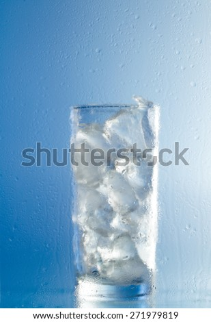 Water glass with ice cubes isolated on blue background