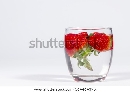 Water glass with several floating strawberries, blank space at left