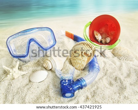 Water goggles and beach toys in the sand - stock photo