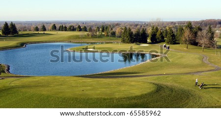 Water hazard surrounds the green on the golf course - stock photo