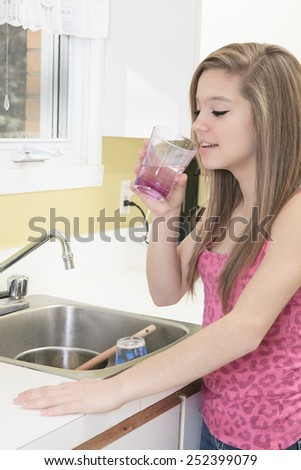 water, healthcare and happiness concept - smiling teenager with glass of water at home