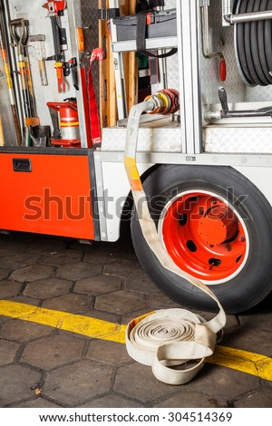 Water hose connected to truck at fire station - stock photo